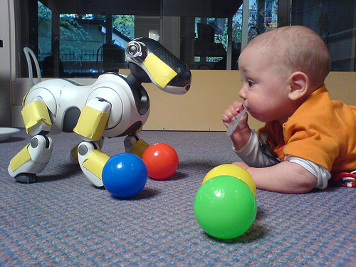 A seven month old infant interacting with an Aibo II, by loetzsch