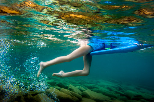 Little Girl Underwater With Surf Board