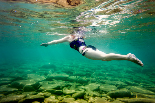 Underwater woman swimming in rocky lake