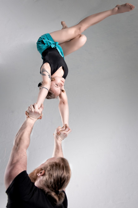 Image of pair acrobats, male is carrying female who is doing a handstand.