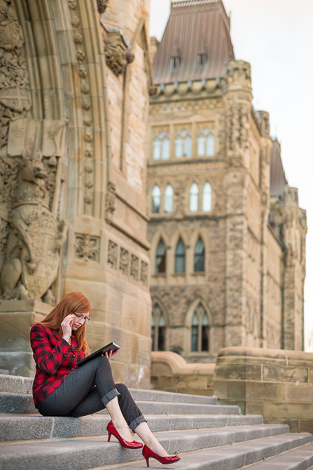Professional woman (40) working on Parliment Hill in Ottawa, Canada with the Canadian parliment buildings in the background.