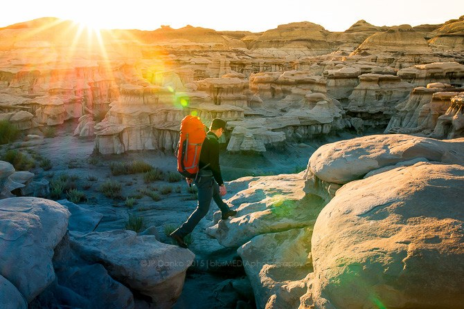 Man (40) hiking in Bisti/De Na Zin Wilderness Area in New Mexico at sunrise.