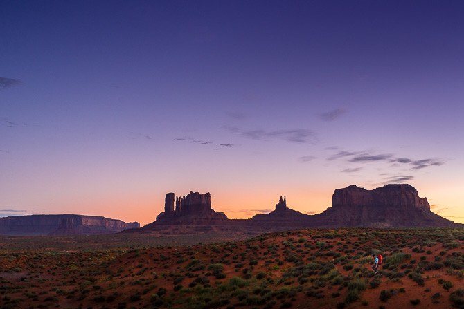 Man (40) hiking at Monument Valley Utah at dusk under colorful evening desert light.