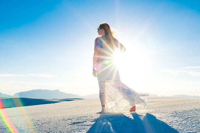 Woman (40) walking in White Sands National Moument, New Mexico in late afternoon with vibrant blue sky (polarized).