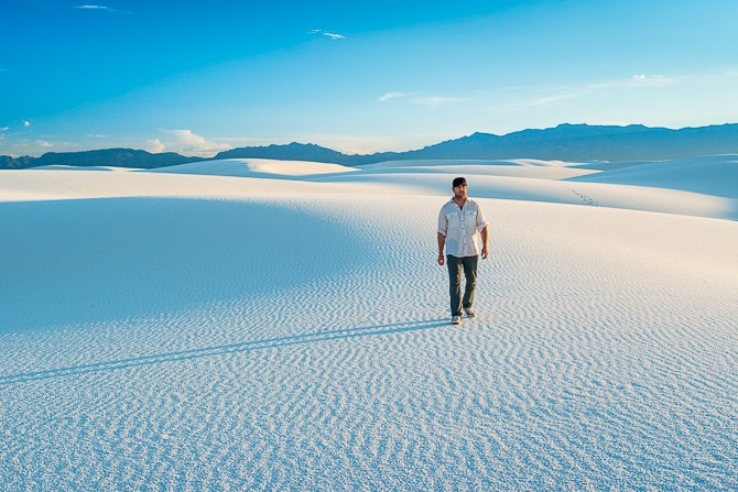 Man (40) hiking on white sand dunes with vibrant clear blue sky in White Sands National Monument New Mexico
