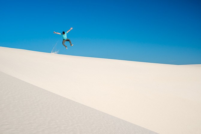 Man (40) jumping off of top of sand dune in White Sands National Monument, New Mexico with pure blue sky.