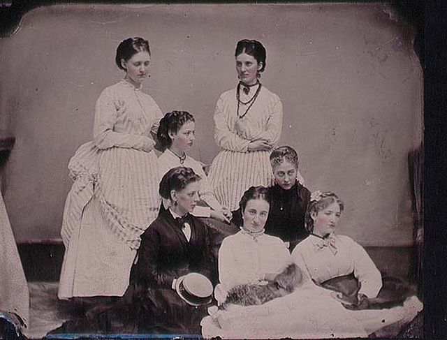 Hand-tinted tintype of seven fashionably attired and impeccably coiffeured young women, possibly sisters. Made available by National Library via Flickr Commons.