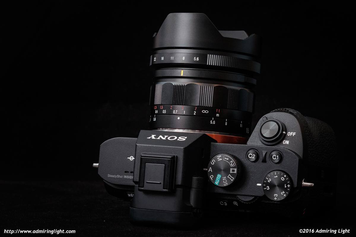 The lens has a built-in metal lens hood and nicely made aperture and focus rings.