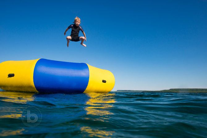 Boy (8) jumping into Georgian Bay (freshwater lake) at cottage in summer from a water trampoline.