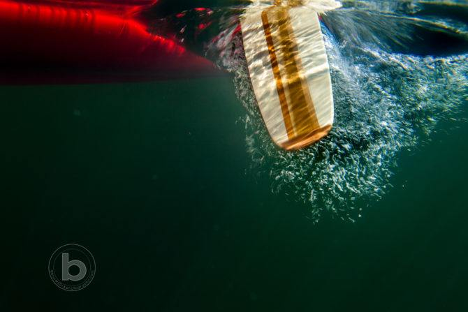Red canoe with canoe paddle underwater in northern lake.