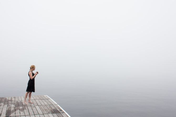 Woman with her morning coffee on the dock at the cottage on a foggy lake.