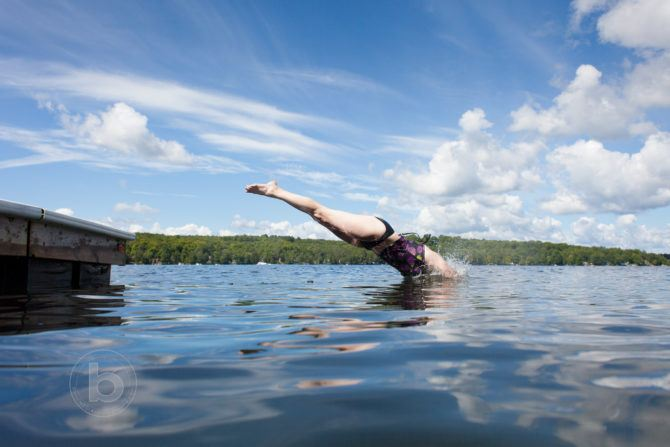 Woman diving into a cottage lake from the dock.
