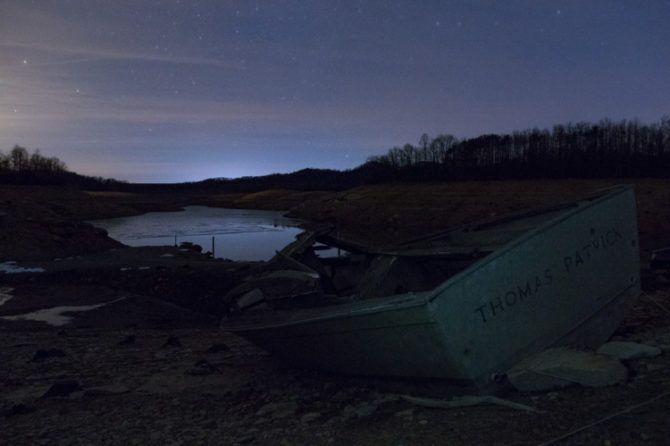 A flashlight covered with a plastic shopping bag lit the corner of the boat to provide more subdued lightning that would blend with the highly reflective surrounding land. The light was on during the entire 15 second exposure at ISO 6400 and f/3.5.