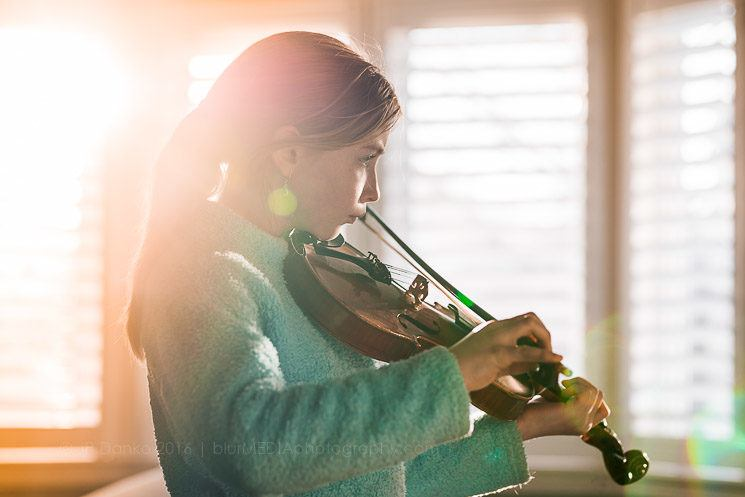 Girl Practicing Violin Music In Sunny Window At Home In Livingro