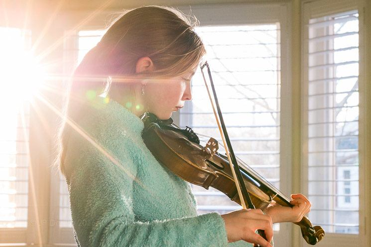 Girl (10) practicing violin at home in a sunny window.