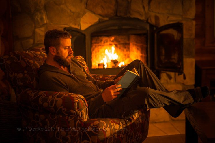Man (40) sitting by a warm open fire at a log cabin ski chalet in Mont Tremblant, Quebec, Canada