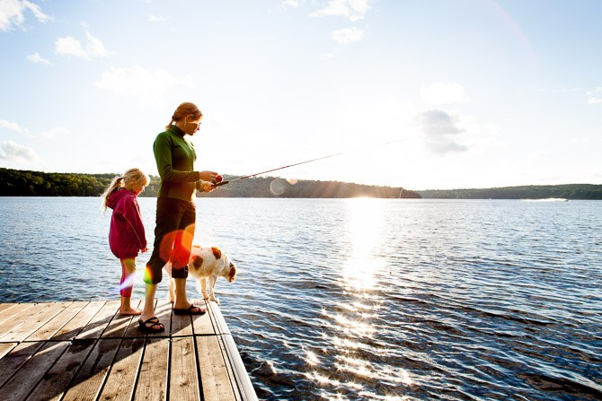 Mother, daughter and dog fishing from a dock on a quiet cottage lake.