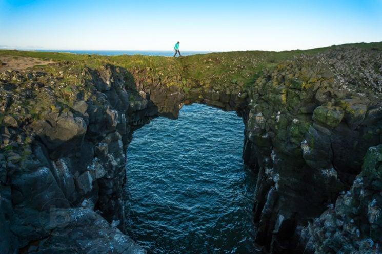 Woman (40) walking across the Arnarstapi Sea Arch, Snaefellsnes Peninsula Iceland
