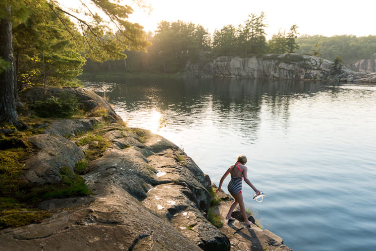 Girl in bathing suit on the rocky shore of lake near Killarney Provincial Park