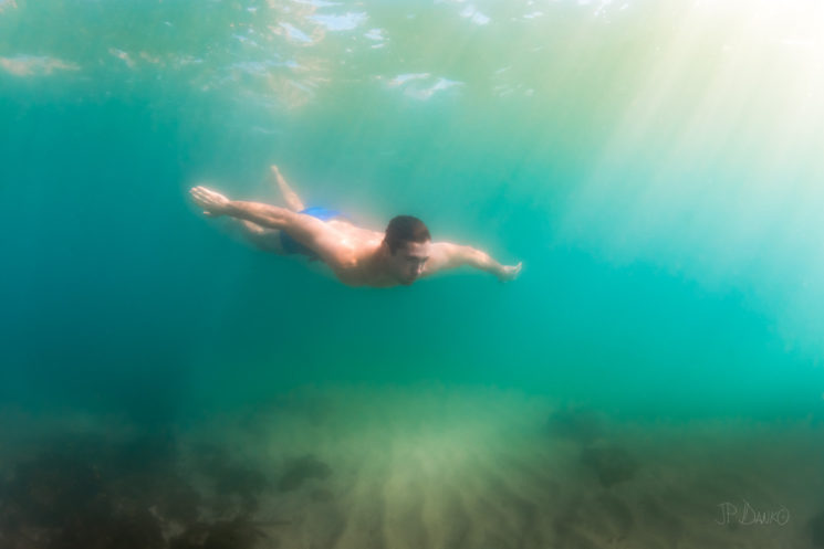 Man in swimsuit diving exploring shallow blue green waters of Lake Ontario