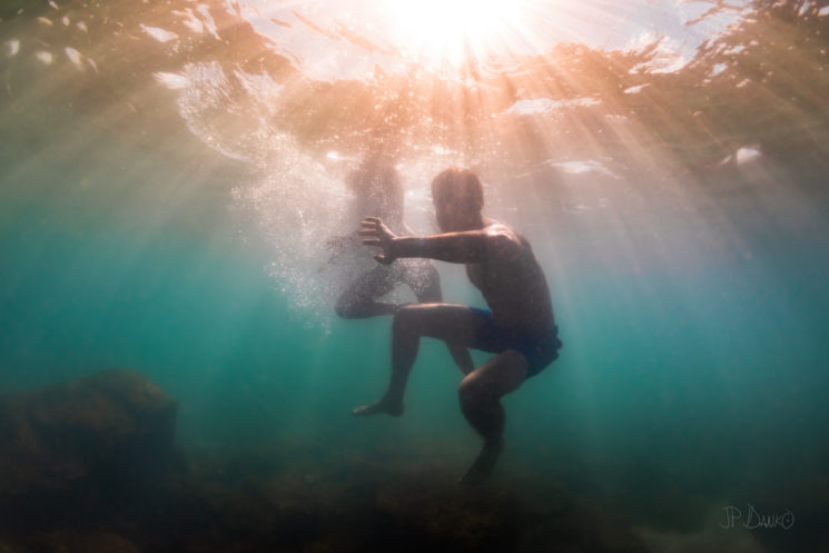 Man and woman together diving exploring blue green shallow waters of Lake Ontario