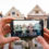 """Man using a smartphone to photograph the """"Painted Ladies"""" homes in San Francisco"""